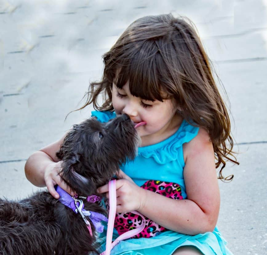child cuddling pet dog